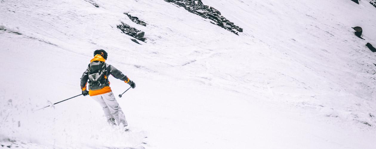 Skifahrer in Skihose und Skijacke auf Piste