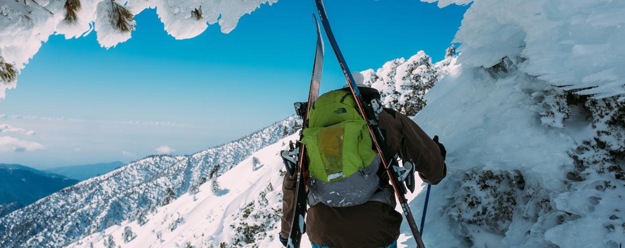 Skifahrer mit Rucksack, Ski und Skijacke