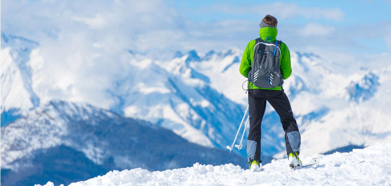 Mann steht auf einem verschneiten Gipfel